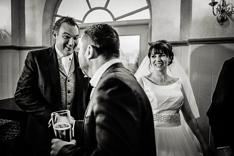 The couple smile at guests