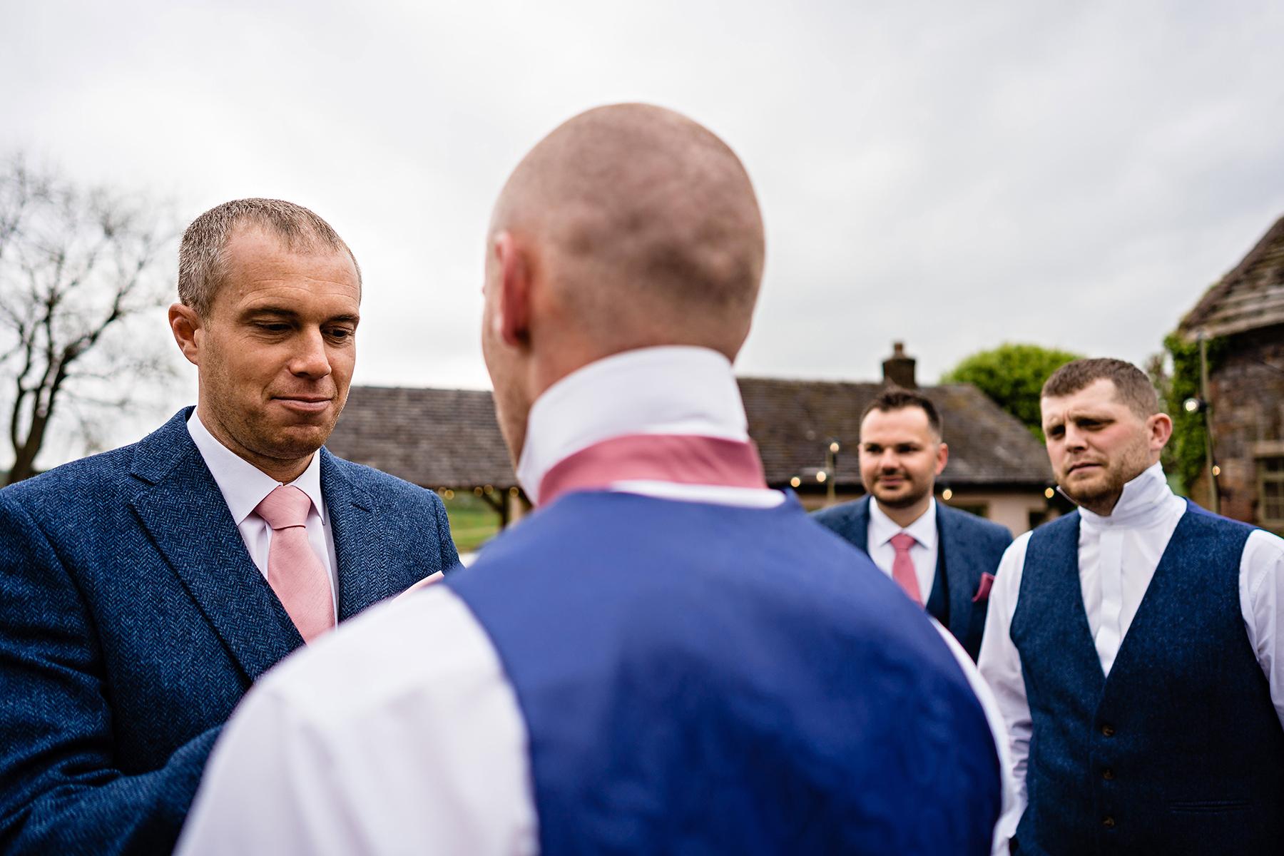 Groom tying his groomsmans tie