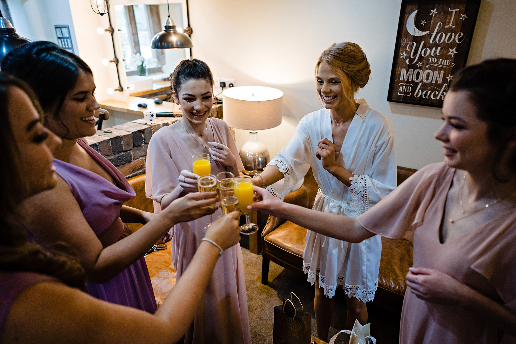 The bridal party cheers during bridal prep