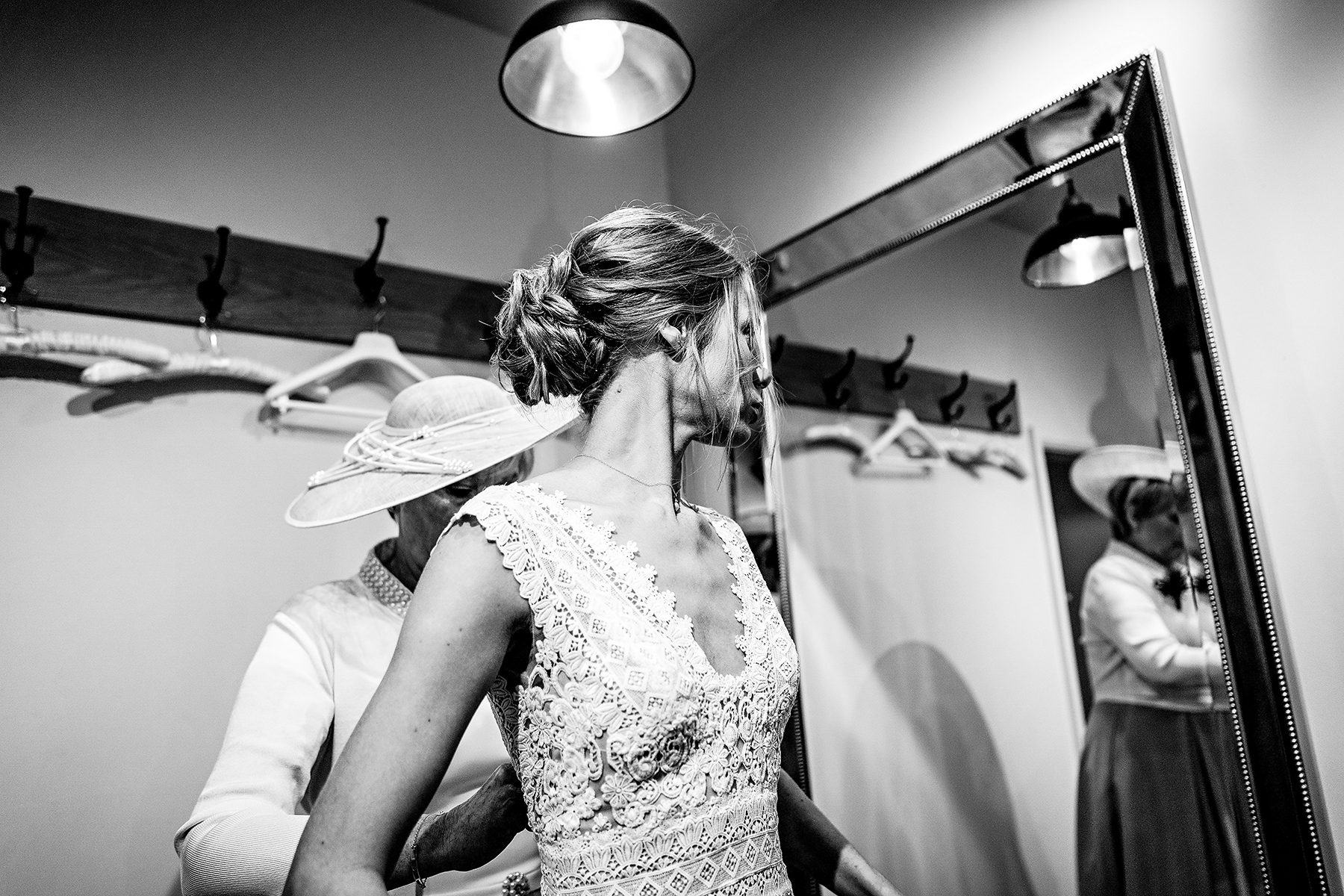 Bride looking in the mirror and wearing her dress