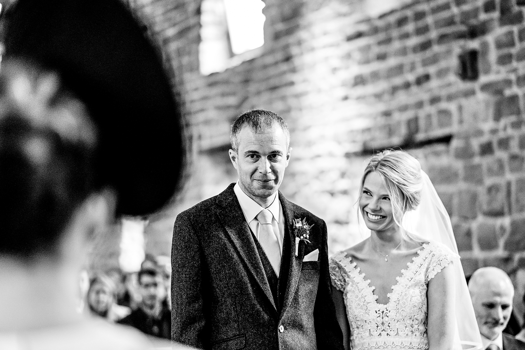 a black and white wedding photograph of the couple listening to a speech