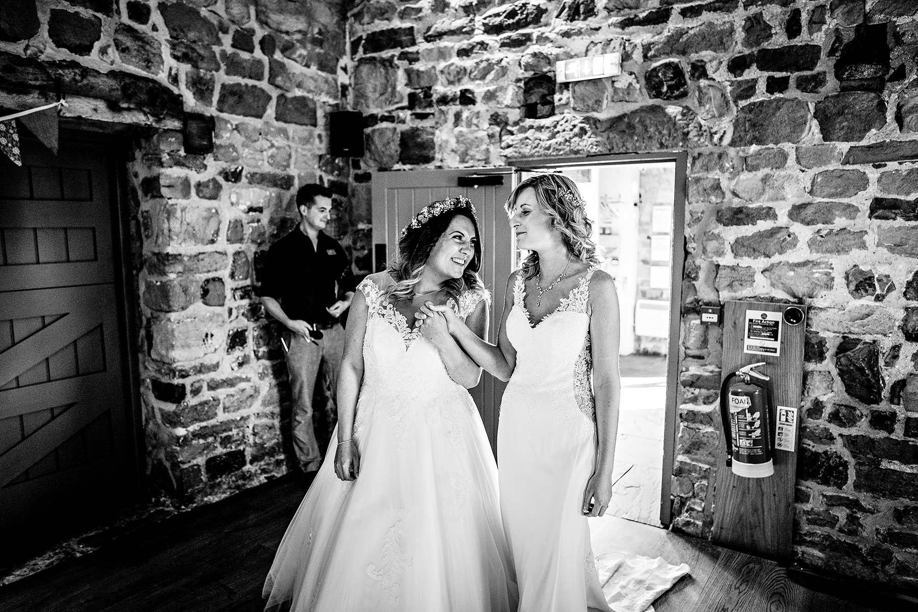 Two brides enter the wedding barn