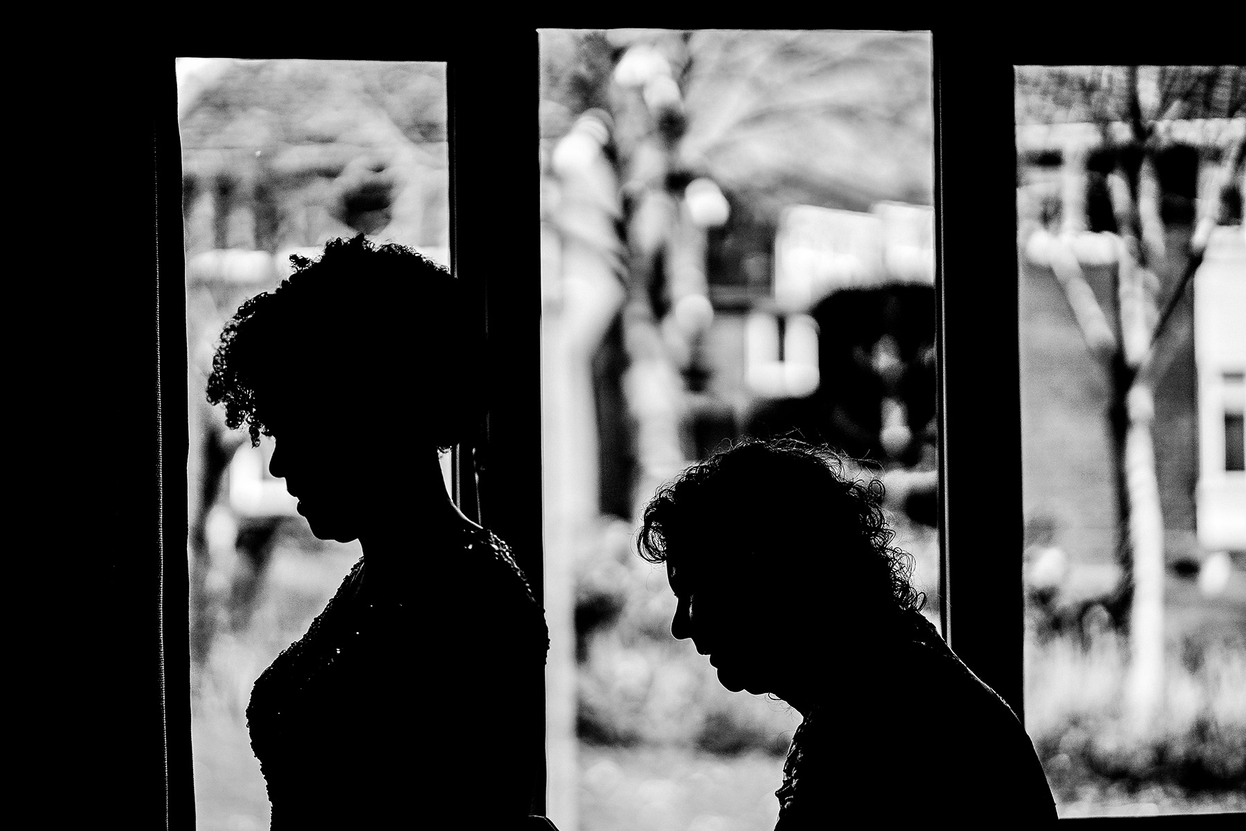 silhouette of the bride having dress done up