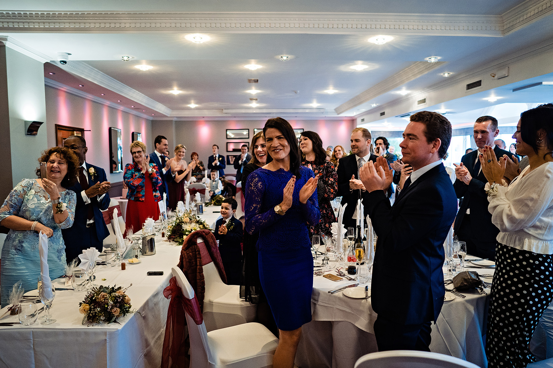 Guests clap as the couple walk into the Acton Suite