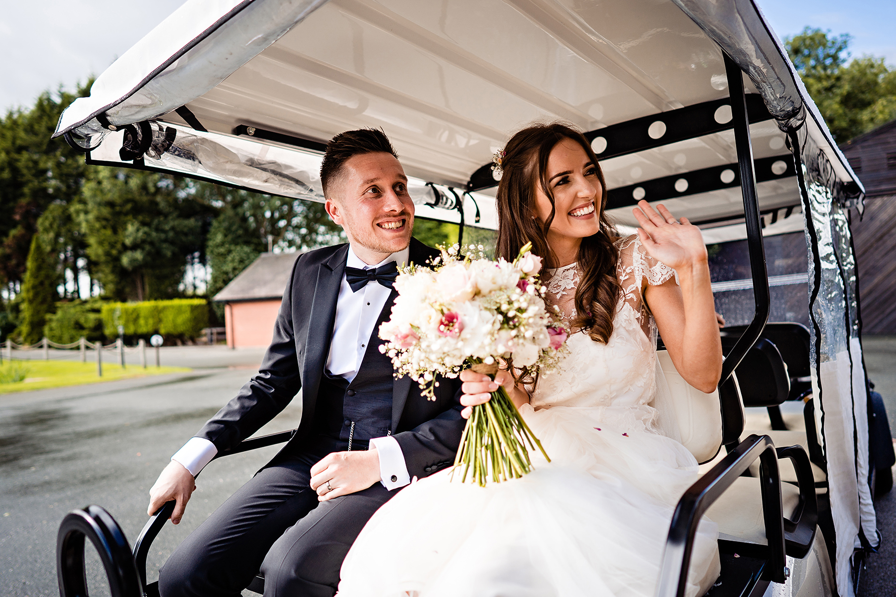 bride and groom leaving the ceremony barn in the golf cart