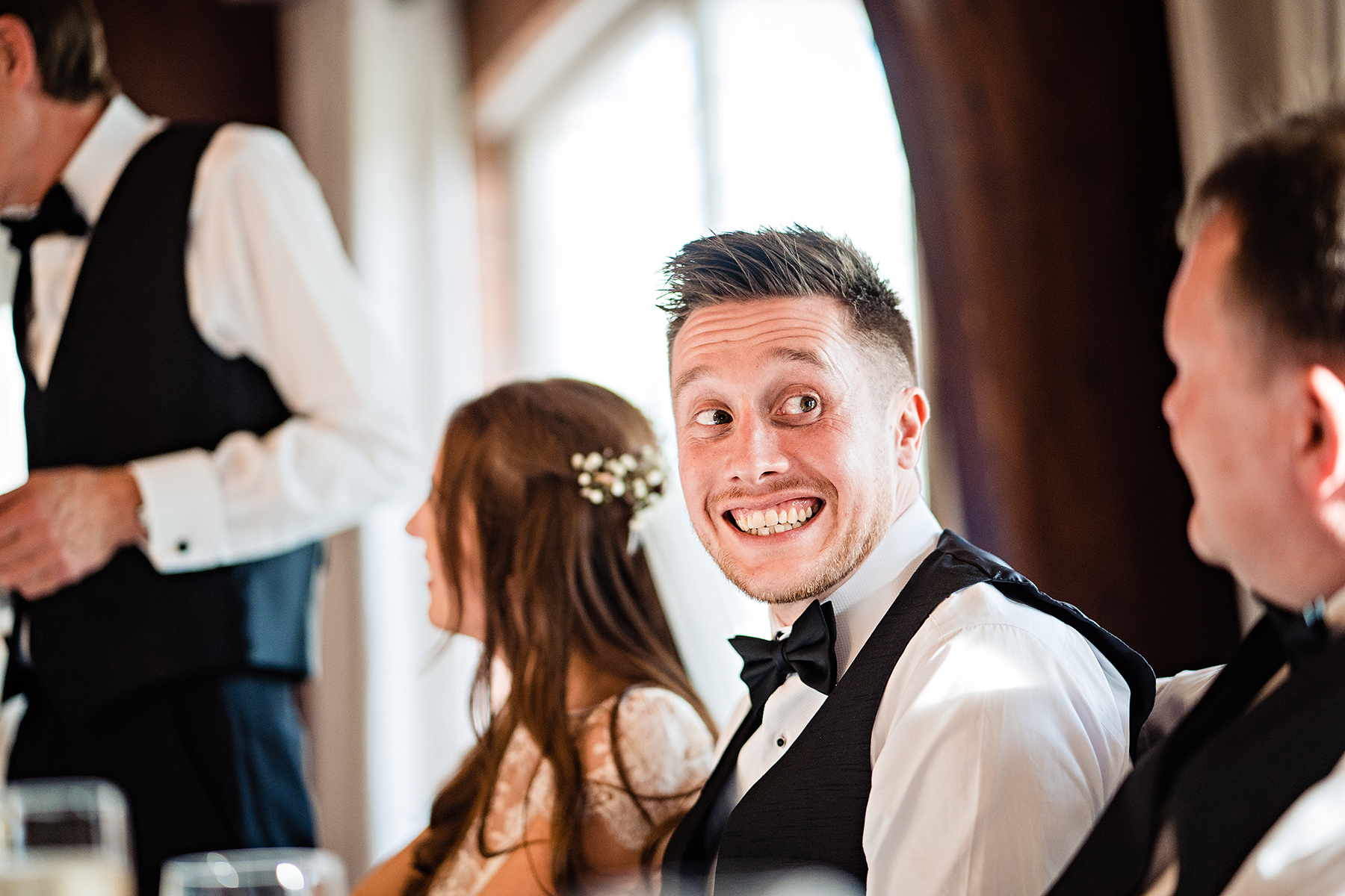 groom smiling at a guest
